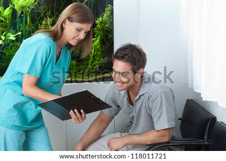 Female dentist showing something to male patient on clipboard at clinic - stock photo
