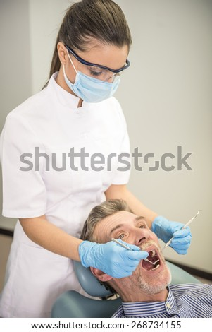 Female dentist with his senior client examining a patient's teeth in dental clinic.