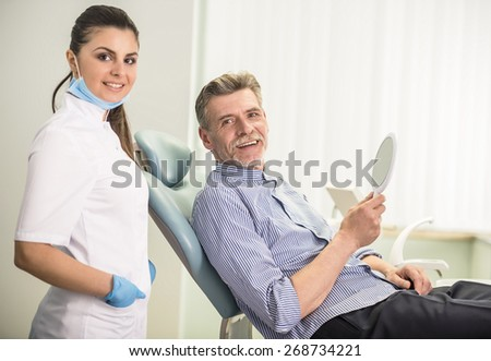 Female dentist with his senior client in dental clinic and looking at camera. - stock photo