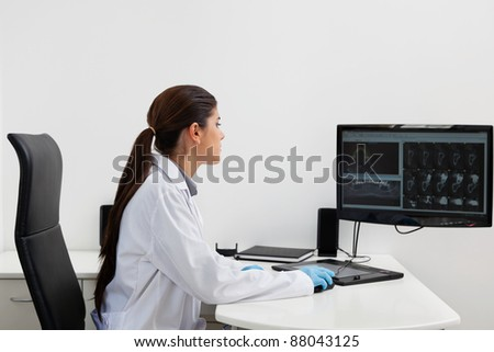 Female dentist with teeth x-ray on screen