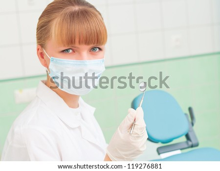female dentists in protective mask holds a dental tool, doctors at work - stock photo