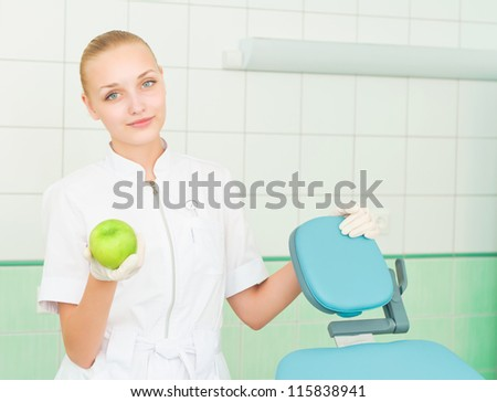 female dentists shows green apple, health care - stock photo