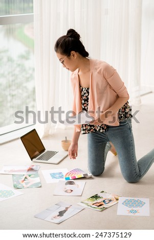 Female designer choosing photos for her project