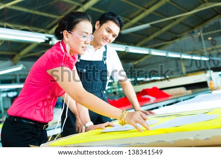 Female Designer or a seamstress and worker or production manager look at pattern on a table in a textile factory - stock photo