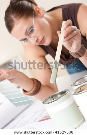 Female designer with can of paint choosing color - stock photo