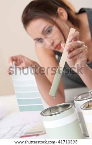 Female designer with can of paint choosing color at office - stock photo