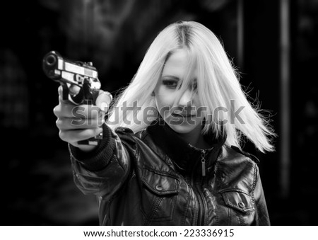 Female detective shooting with gun on the street at night. - stock photo