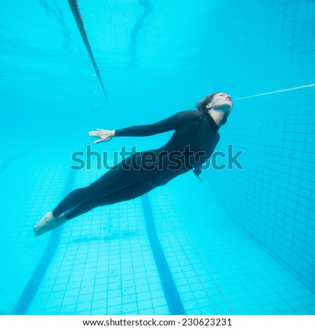 Female diver appearing to fly underwater in swimming pool - stock photo