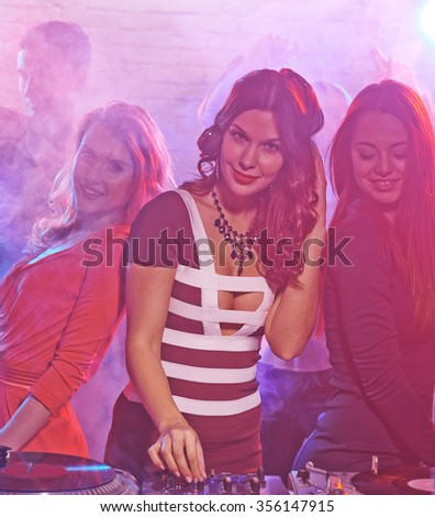 Female dj playing music in night club - stock photo