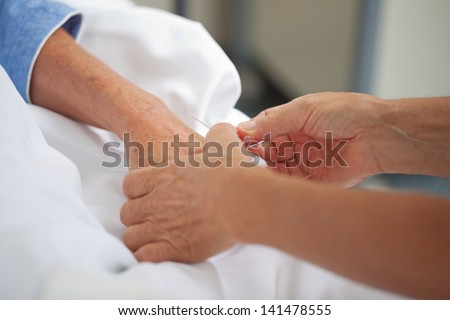Female doctor adjusting drip on patients hand in hospital - stock photo