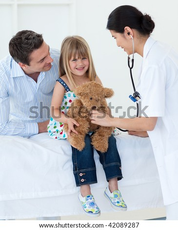 Female doctor and happy little girl examing a teddy bear in the hospital - stock photo