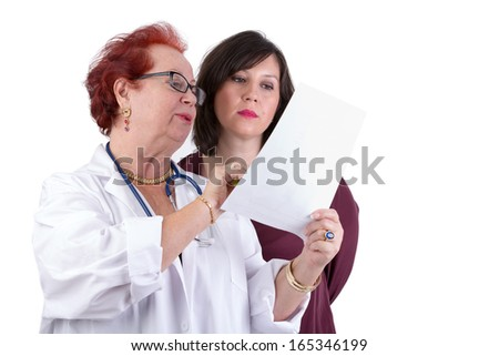 Female Doctor and her female patient discussing exam results, might be her blemish on her face - stock photo