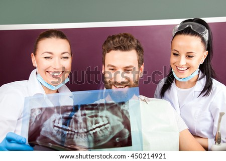 Female doctor and her smiling assistant showing teeth x-ray to male patient in dental hospital. Handsome men with beard sitting in medical chair and looking at the picture. - stock photo