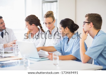 Female doctor and nurse discussing over laptop with colleagues in hospital - stock photo