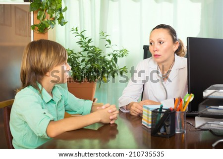 Female doctor and patient boy talking in the office - stock photo