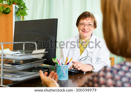 Female  doctor and patient discuss something in a doctor's office - stock photo