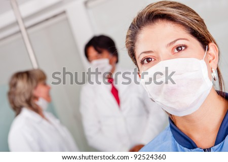Female doctor at the hospital wearing a facemask - stock photo