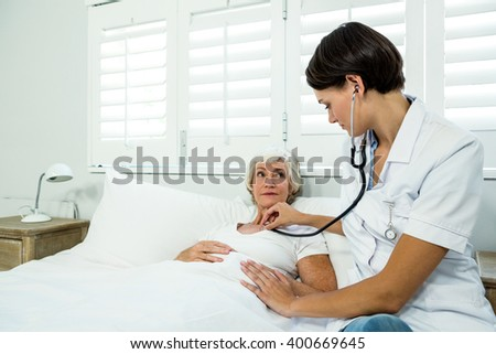 Female doctor auscultating aged woman against window at home - stock photo