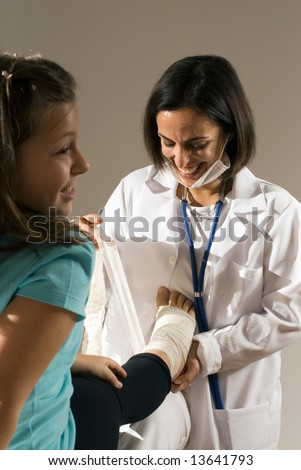 Female Doctor bandages a young girl's foot. The doctor's mask is partially on her face and you can see she is smiling while she works. The girl is also smiling. Vertically framed photograph - stock photo