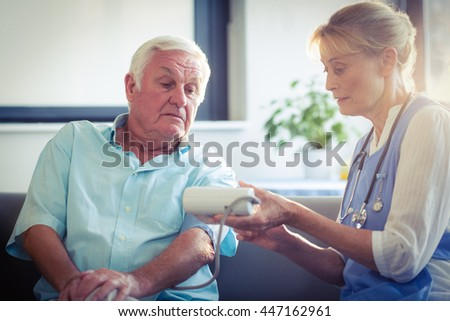 Female doctor checking blood pressure of senior man at home