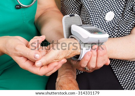 Female doctor checking senior woman blood pressure - stock photo