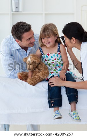 Female doctor checking smiling girl's ears in the hospital - stock photo