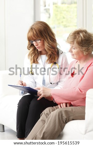 Female doctor consulting with senior patient in small clinic. - stock photo