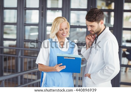 Female doctor discussing with male colleague at hospital - stock photo