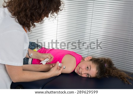 Female doctor doing vaccine to her young patient - stock photo