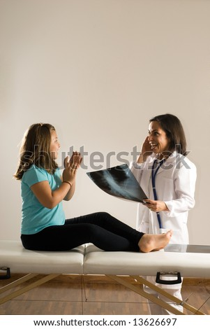 Female Doctor examines a young girl's x-ray while the barefoot girl sits on the examining table. Both people are smiling and appear happy with the results. Vertically framed photograph - stock photo