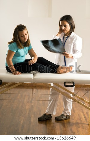 Female doctor examines an x-ray while a barefoot young girl sitting on an examining table looks down at her leg. Both the Doctor and the girl appear worried. Vertically framed photograph - stock photo