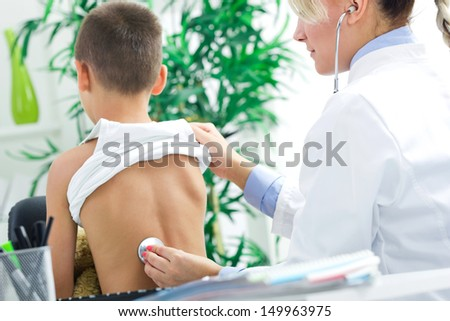 female doctor examines the boy's back with stethoscope - stock photo