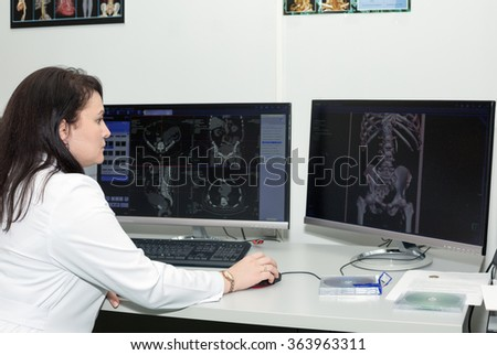Female doctor examining an CT scanner results - stock photo