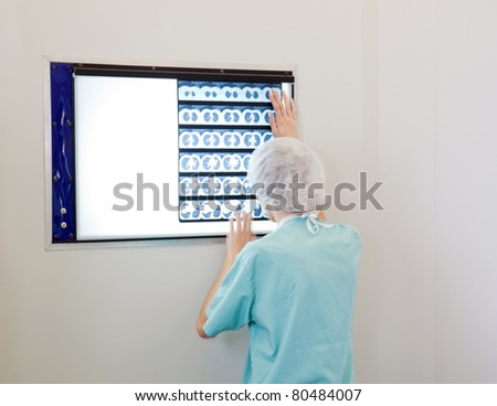 Female doctor examining an X-Ray image of patient - stock photo