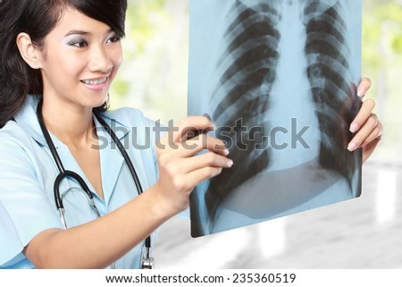 Female doctor examining an x-ray isolated over white background - stock photo
