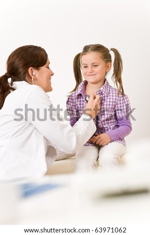 Female doctor examining child with stethoscope at surgery - stock photo