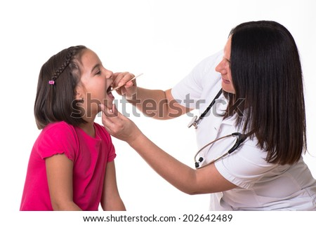 Female doctor examining child with tongue depressor at surgery. - stock photo