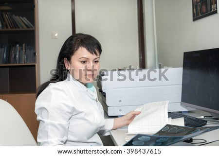 Female doctor examining CT scanner results - stock photo