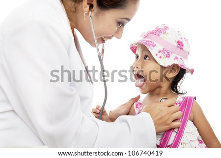 Female doctor examining cute little girl using stethoscope - stock photo