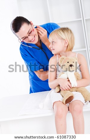 Female doctor examining little girl - stock photo