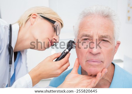 Female doctor examining senior patients ear with otoscope in clinic - stock photo