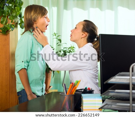 Female doctor examining throat of teenage boy in clinic  - stock photo