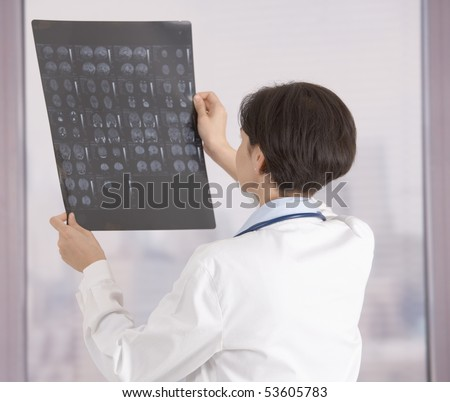 Female doctor examining x-ray in front of office window. - stock photo