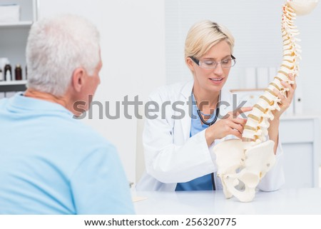 Female doctor explaning anatomical spine to senior male patient in clinic - stock photo