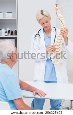 Female doctor explaning spine model to senior male patient in hospital - stock photo