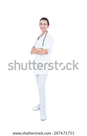 Female doctor folding arms against white background - stock photo