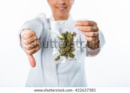 Female doctor giving a thumbs down while holding a bag of marijuana buds. She is wearing a lab coat and is unrecognizable. The doctor is out of focus.  - stock photo