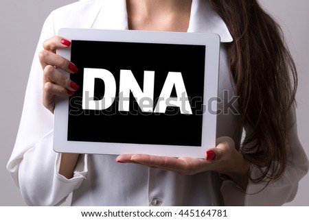 Female doctor holding a tablet with the text: DNA - stock photo