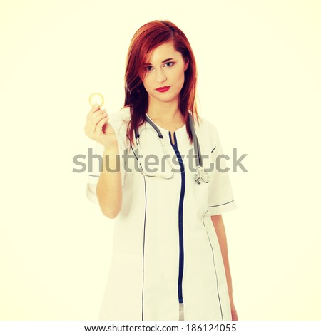 Female Doctor holding condom for aids prevention and birth control - stock photo
