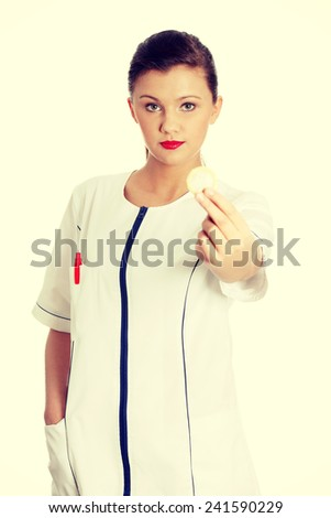 Female doctor holding condom in hand. - stock photo